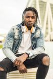 Outdoor portrait of a handsome and attractive young African man with music headphones on the street. Concept of technology stock photo