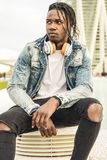 Outdoor portrait of a handsome and attractive young African man with music headphones on the street. Concept of technology stock photos
