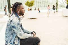 Outdoor portrait of a handsome and attractive young African man with music headphones on the street. Concept of technology stock photography