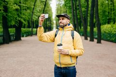 Outdoor portrait of handsome guy with thick beard wearing yellow anorak and jeans holding rucksack, coffee and smartphone making s royalty free stock photos