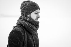 Outdoor portrait of handsome man in gray coat. Fashion photo. Beauty winter snowfall style. Black and White.  Stock Photos