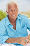 Outdoor Portrait of A Handsome Senior Man. Portrait of a happy attractive handsome senior man sitting down outside and smiling Stock Photography