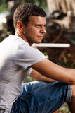Outdoor portrait of a handsome young man in jeans and gray t-shirt. Stock Photos