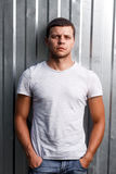 Outdoor portrait of a handsome young man in jeans and gray t-shirt. Stock Photo