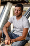 Outdoor portrait of a handsome young man in jeans and gray t-shirt. Stock Image