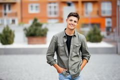 Outdoor portrait of handsome young man walking on the street, looking at camera and smile. Outdoor portrait of handsome young man walking on the street, looking Stock Images