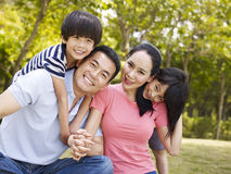 Outdoor portrait of happy asian family. Asian family with two children taking a family photo outdoors in a city park