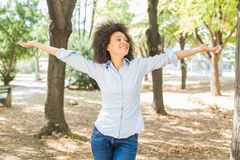 Happy Beautiful Young African Woman With Open Arms In Nature stock images
