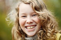 Outdoor portrait of happy blond girl. Outdoor portrait of smiling blond girl in autumn park Stock Photo