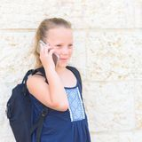Outdoor portrait of happy girl 8-9 year old talking on phone. royalty free stock images
