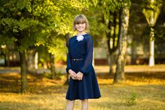 Outdoor portrait of happy little schoolgirl in school uniform in park. Back to school. royalty free stock photo