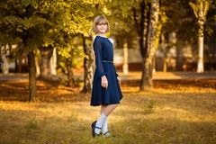 Outdoor portrait of happy little schoolgirl in school uniform in park. Back to school stock images