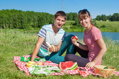 Outdoor portrait of happy loving couple having a picnic at the lake Stock Image