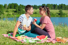 Outdoor portrait of happy loving couple having a picnic at the lake Royalty Free Stock Image