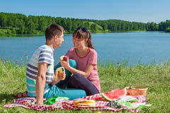Outdoor portrait of happy loving couple having a picnic at the lake Stock Photo