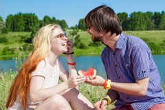 Outdoor portrait of happy loving couple at the lake, which is eating watermelon Royalty Free Stock Photos