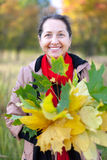 Happy mature woman with maple posy Stock Images