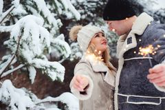 Outdoor portrait of happy romantic couple celebrating Christmas with burning fireworks. In snowy forest. Runaway and travel on Holidays concept stock photos