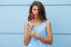 Outdoor portrait of happy young beautiful brunette woman in striped summer dress posing with red heart lollipop against metal geom Royalty Free Stock Photography