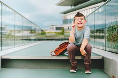 Outdoor portrait of funny little schoolboy. Outdoor portrait of happy young kid boy. Fashion schoolboy resting outside. Back to school concept Stock Images