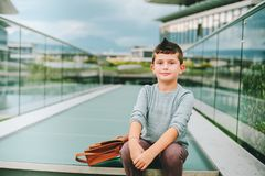 Outdoor portrait of funny little schoolboy. Outdoor portrait of happy young kid boy. Fashion schoolboy resting outside. Back to school concept Stock Photo