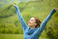 Outdoor portrait of a happy young woman. Beautiful young woman outdoor, happy with raised arms enjoying the free time. Spring woman in blue woolen sweater Royalty Free Stock Photography