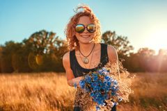 Outdoor portrait of happy young woman with red curly hair holding flowers. Summer holidays. royalty free stock photo