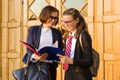 Outdoor portrait of high school teacher with schoolgirl near the front door of the school stock photo