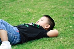 Little asian boy. Outdoor portrait of a little asian fat boy, Play in the park,Lying on the lawn and rest stock photos