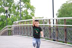 Little asian boy. Outdoor portrait of a little asian fat boy, Play in the park,Running on the bridge royalty free stock photography