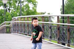 Little asian boy. Outdoor portrait of a little asian fat boy, Play in the park,Running on the bridge royalty free stock photo