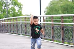 Little asian boy. Outdoor portrait of a little asian fat boy, Play in the park,Running on the bridge stock photography