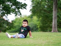 Little asian boy. Outdoor portrait of a little asian fat boy, Play in the park,Sit on the lawn and rest royalty free stock photography