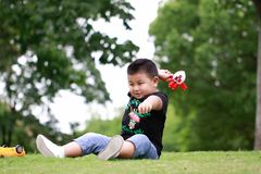 Little asian boy. Outdoor portrait of a little asian fat boy, Play in the park,Sit on the lawn and rest royalty free stock photos