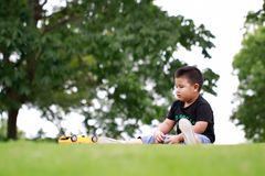 Little asian boy. Outdoor portrait of a little asian fat boy, Play in the park,Sit on the lawn and rest royalty free stock image