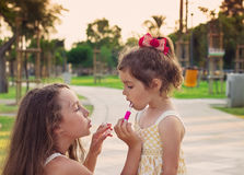 Outdoor portrait of Little beautiful girls painting lips of pink. Outdoor portrait of Little beautiful girls painting lips of  lipstick Stock Image