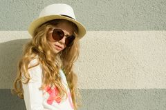 Outdoor portrait little blonde girl with long curly hair, sunglasses in straw hat. Gray textured wall background, copy space.  Royalty Free Stock Images