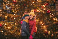 Outdoor portrait of little children next to Christmas tree with lights. Wearing warm jackets and hats stock photos