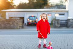 Outdoor portrait of little cute toddler girl in red coat aon spring sunny day with push wooden toy. Healthy happy baby. Child walking in the city. Fashion royalty free stock photos