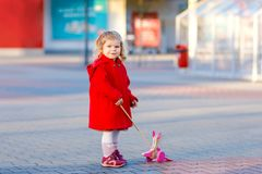 Outdoor portrait of little cute toddler girl in red coat aon spring sunny day with push wooden toy. Healthy happy baby. Child walking in the city. Fashion stock photos