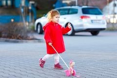 Outdoor portrait of little cute toddler girl in red coat aon spring sunny day with push wooden toy. Healthy happy baby. Child walking in the city. Fashion royalty free stock image