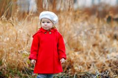 Outdoor portrait of little cute toddler girl in red coat and white fashion hat barret. Healthy happy baby child walking. In the park on cold day. Fashion royalty free stock images