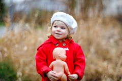 Outdoor portrait of little cute toddler girl in red coat and white fashion hat barret with toy doll. Healthy happy baby. Child walking in the park on cold day royalty free stock photography