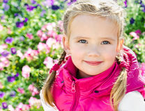 Outdoor portrait of little girl near the flowers Stock Images
