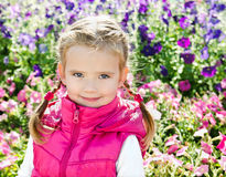 Outdoor portrait of little girl near the flowers Stock Photography