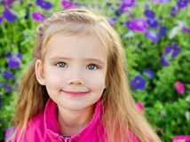 Outdoor portrait of little girl near the flowers Royalty Free Stock Photos