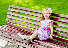 Outdoor portrait of little girl sitting on a bench Stock Photos