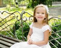 Outdoor portrait of little girl sitting on a bench Royalty Free Stock Photos