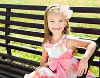 Outdoor portrait of little girl sitting on a bench Royalty Free Stock Photo