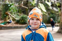 Outdoor portrait of little kid boy in spring or autumn colorful clothes. Happy boy having fun in a zoo. Smiling child Royalty Free Stock Image